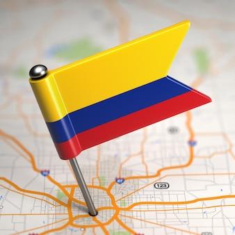 Kleine vlag van colombia op de achtergrond van een kaart met selectieve aandacht.