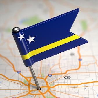 Kleine vlag van curaçao op de achtergrond van een kaart met selectieve aandacht.