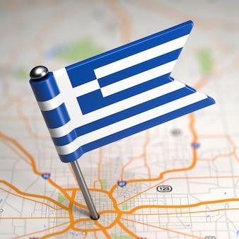 Kleine vlag van de helleense republiek griekenland op de achtergrond van een kaart met selectieve aandacht.