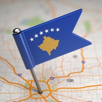 Kleine vlag van de republiek kosovo op de achtergrond van een kaart met selectieve aandacht.