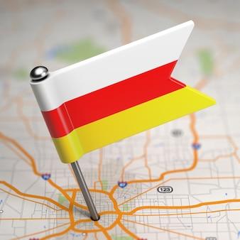 Kleine vlag van de republiek zuid-ossetië op de achtergrond van een kaart met selectieve aandacht.