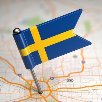 Kleine vlag van het koninkrijk zweden op de achtergrond van een kaart met selectieve aandacht.