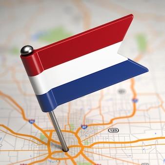 Kleine vlag van nederland geplakt op de kaartachtergrond met selectieve aandacht.