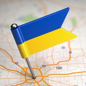 Kleine vlag van oekraïne geplakt op de kaartachtergrond met selectieve aandacht.
