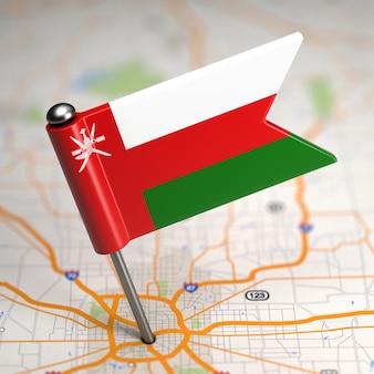 Kleine vlag van oman op de achtergrond van een kaart met selectieve aandacht.
