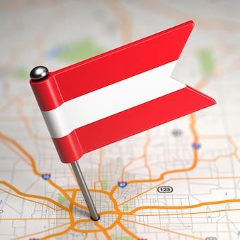 Kleine vlag van oostenrijk geplakt op de kaartachtergrond met selectieve aandacht.