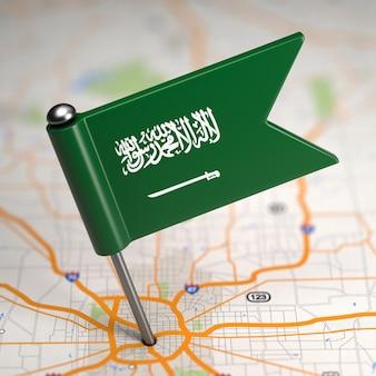 Kleine vlag van saoedi-arabië op de achtergrond van een kaart met selectieve aandacht.