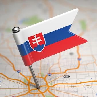 Kleine vlag van slowakije op de achtergrond van een kaart met selectieve aandacht.