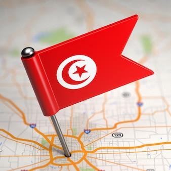 Kleine vlag van tunesië op de achtergrond van een kaart met selectieve aandacht.