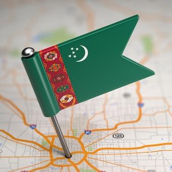 Kleine vlag van turkmenistan op de achtergrond van een kaart met selectieve aandacht.