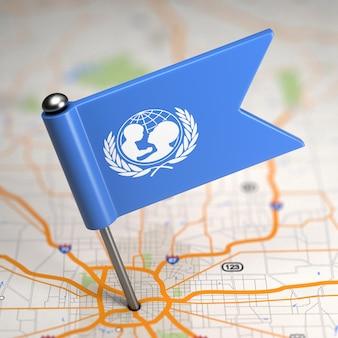 Kleine vlag van unicef op de achtergrond van een kaart met selectieve aandacht.