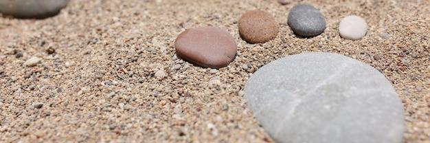 Kleine voeten zijn gemaakt van stenen op een fornuis op zeestrandclose-up