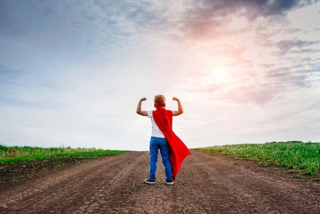 Kleine voorschoolse jongen, speelt de superheld buitenshuis