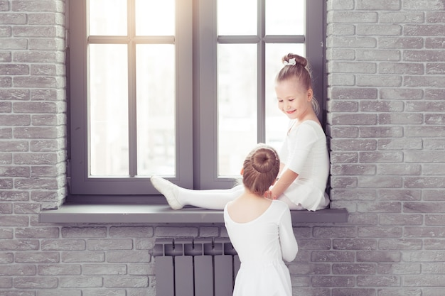 Kleine vrienden kinderen dansen ballet zittend op de vensterbank en omarmen terwijl ze samen glimlachen