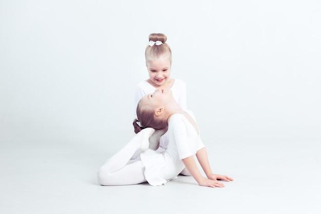 Kleine vrienden kinderen dansen ballet zittend op de vloer en glimlachen samen