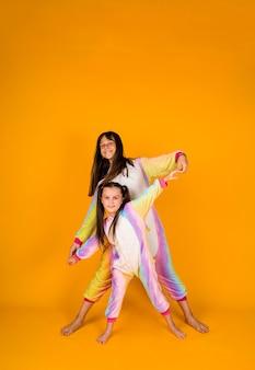 Kleine vriendinnen in kigurumi staan op een gele achtergrond met een plek voor tekst