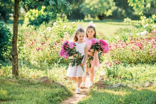 Kleine vriendinnen met een groot boeket pioenrozen. kinderen lopen in de zomer in het park met bloemen.