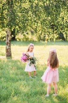 Kleine vriendinnen worden gefotografeerd met een groot boeket pioenrozen. kinderen lopen in de zomer in het park met bloemen, spelen fotograaf en model.