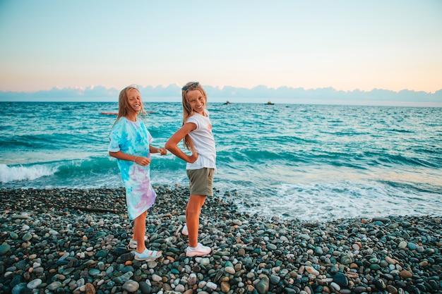 Kleine vrolijke grappige meisjes hebben veel plezier op het tropische strand samen poseren