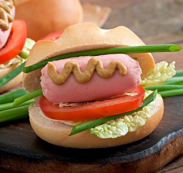 Kleine vrolijke hotdog met worst en tomaat