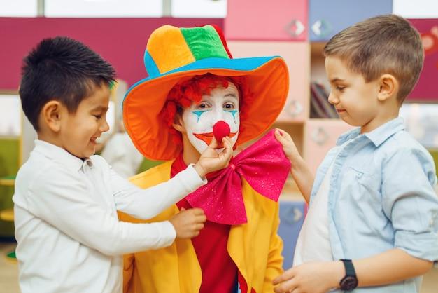 Kleine vrolijke jongen raakt de neus van de rode clown