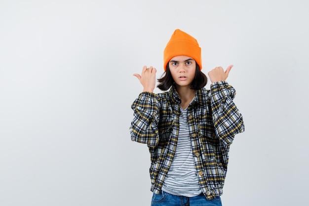 Kleine vrouw die duimen naar beide kanten wijst in t-shirt en jas die aarzelend kijkt