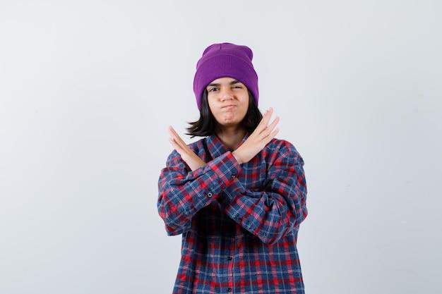 Kleine vrouw die een stopgebaar toont in een geruit overhemd en een muts die er serieus uitziet
