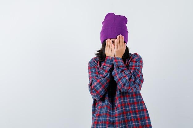 Kleine vrouw die gezicht bedekt met handen in geruit hemd