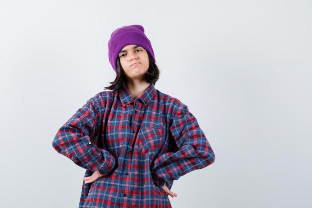 Kleine vrouw die haar handen op de heup houdt in een geruit hemd en een muts die er weemoedig uitziet