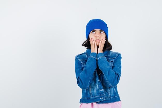 Kleine vrouw die haar handen op de wangen houdt terwijl ze omhoogkijkt in een t-shirt en er attent uitziet