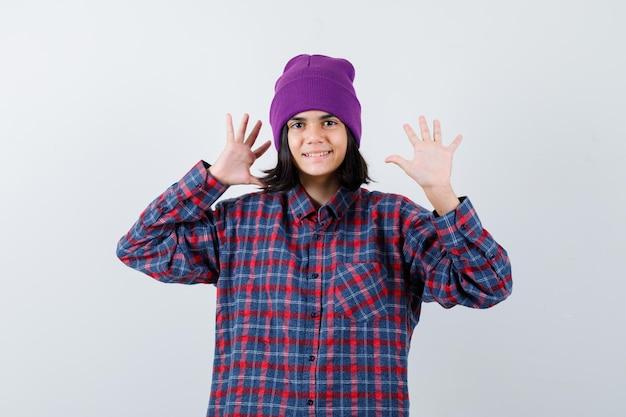 Kleine vrouw die handpalmen in geruit hemd en muts laat zien en er gelukkig uitziet
