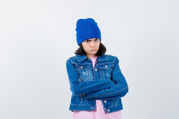Kleine vrouw die met gekruiste armen staat en er serieus uitziet