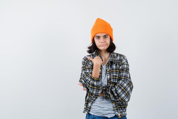 Kleine vrouw die naar zichzelf wijst in een muts met een t-shirtjasje en er trots uitziet