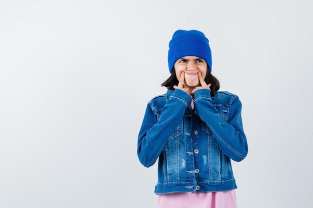 Kleine vrouw die vingers op wangen drukt in t-shirt en spijkerjasje ziet er grappig uit