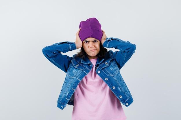 Kleine vrouw hand in hand op haar hoofd in t-shirt spijkerjasje beanie kijkt geërgerd
