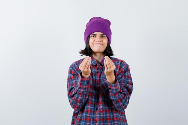 Kleine vrouw in geruit hemd en muts die een italiaans gebaar toont en er verrukt uitziet