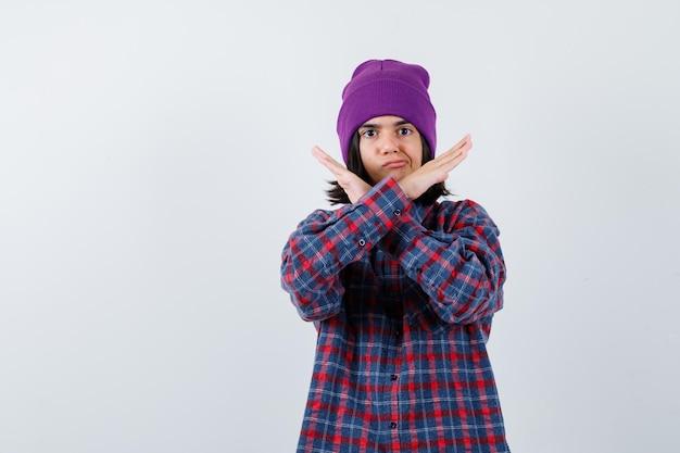 Kleine vrouw in geruit hemd en muts die een stopgebaar laat zien en er serieus uitziet