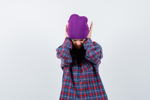 Kleine vrouw in geruit hemd en muts hand in hand op oren en kijkt geïrriteerd
