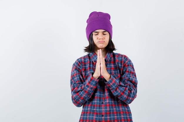Kleine vrouw in geruit hemd en muts met gevouwen handen in een smekend gebaar