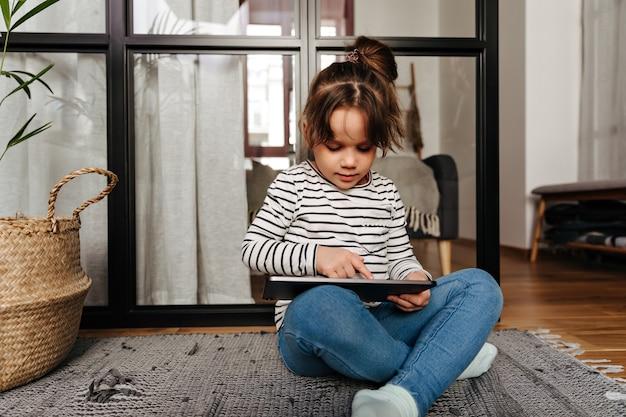 Kleine vrouw in skinny jeans en gestreepte trui trekt in tablet en zit op de vloer in de woonkamer.