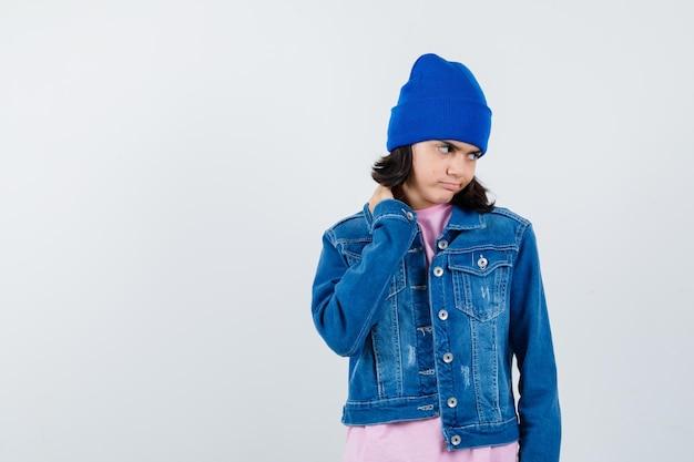 Kleine vrouw in t-shirt en spijkerjasje en muts met hand op nek