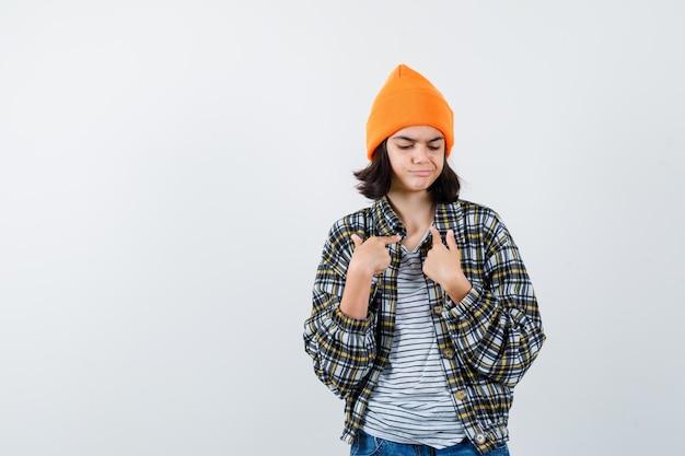 Kleine vrouw in t-shirt jasje muts wijst naar zichzelf en kijkt trots