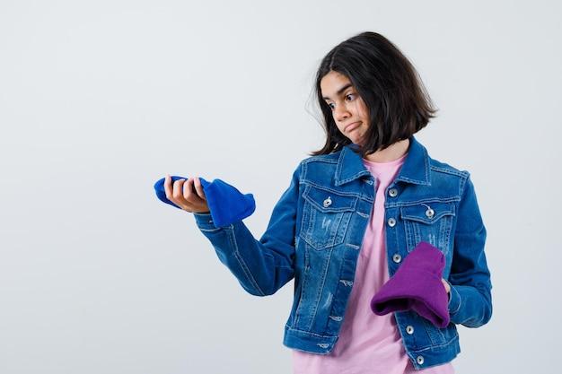 Kleine vrouw kijkt naar beanies in t-shirt spijkerjasje beanie kijkt besluiteloos