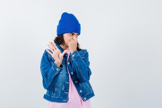 Kleine vrouw knijpt in neus door slechte geur in t-shirt en spijkerjasje en ziet er walgelijk uit