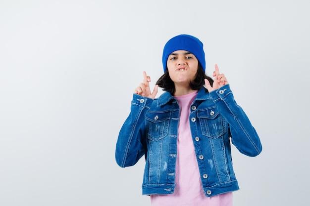Kleine vrouw met gekruiste vingers in t-shirt en spijkerjasje en muts die er schattig uitziet