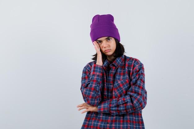 Kleine vrouw met hand op hoofd in geruit overhemd en muts die er attent uitziet