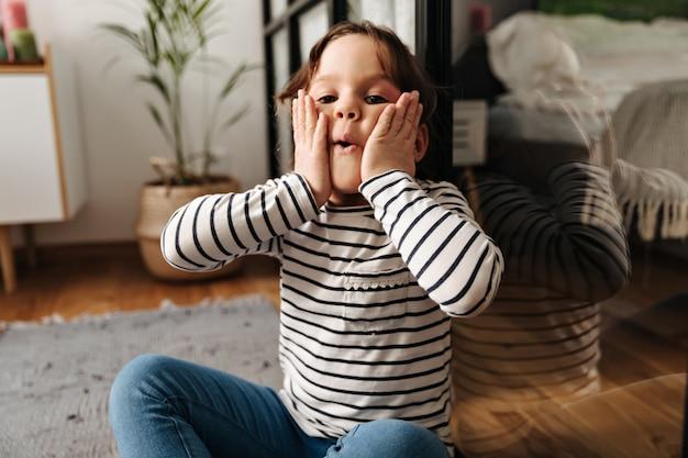 Kleine vrouw ploetert en blaast haar wangen. portret van kind zittend op de vloer.
