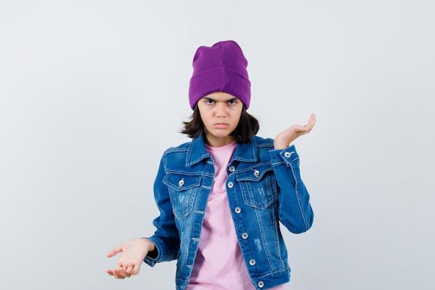 Kleine vrouw spreidt handpalmen uit in t-shirt spijkerjasje beanie ziet er ontevreden uit