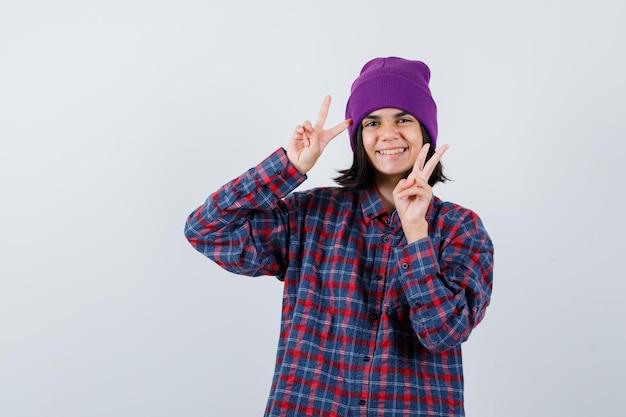 Kleine vrouw toont overwinningsteken in geruit hemd en muts en ziet er vrolijk uit