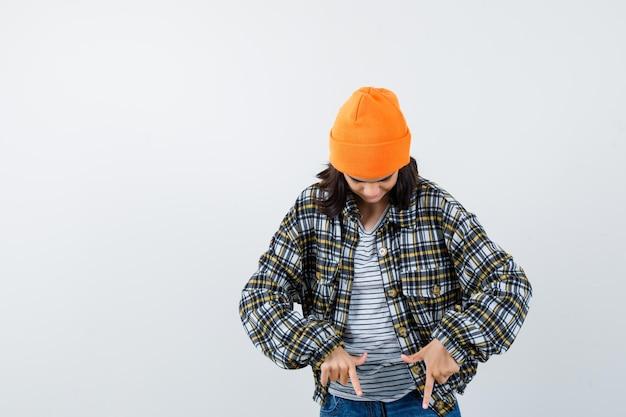 Kleine vrouw wijst naar beneden in t-shirt en jas en muts en ziet er zelfverzekerd uit